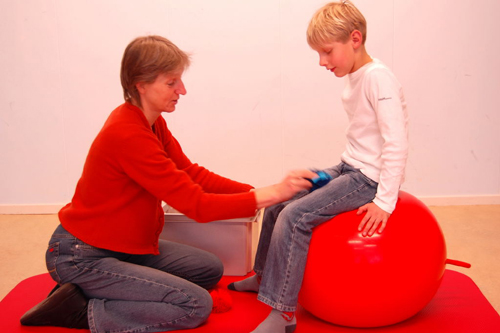sitting on a ball while someon touches you with a cuddly toy